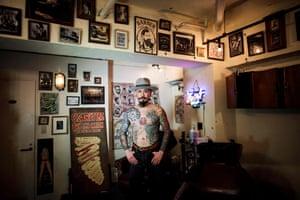 Hairdresser Hirotaka Yamakawa displays his tattoos at a barber shop in Tokyo