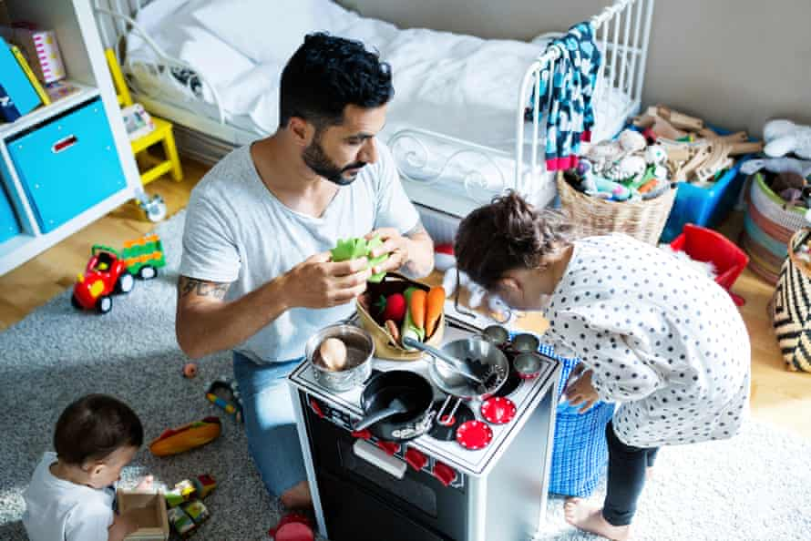 High angle view of father and sons playing with toy kitchen in bedroom at home