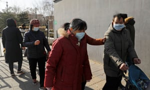 People wearing face masks walk along a street, following new cases of the coronavirus in the country, in Beijing, China 11 January 2021.