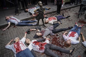 Activists lying on ground covered in fake blood during a rally for action inNew York, US.