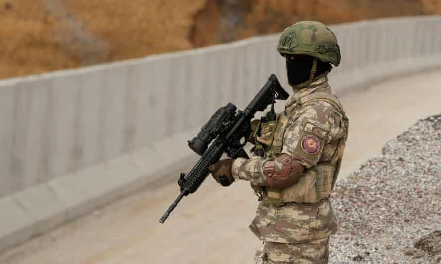 A Turkish commando stands guard near a wall on the border line between Turkey and Iran in Van province.