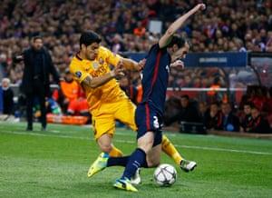 Barcelona's Luis Suarez tackles Atlético's Diego Godin.