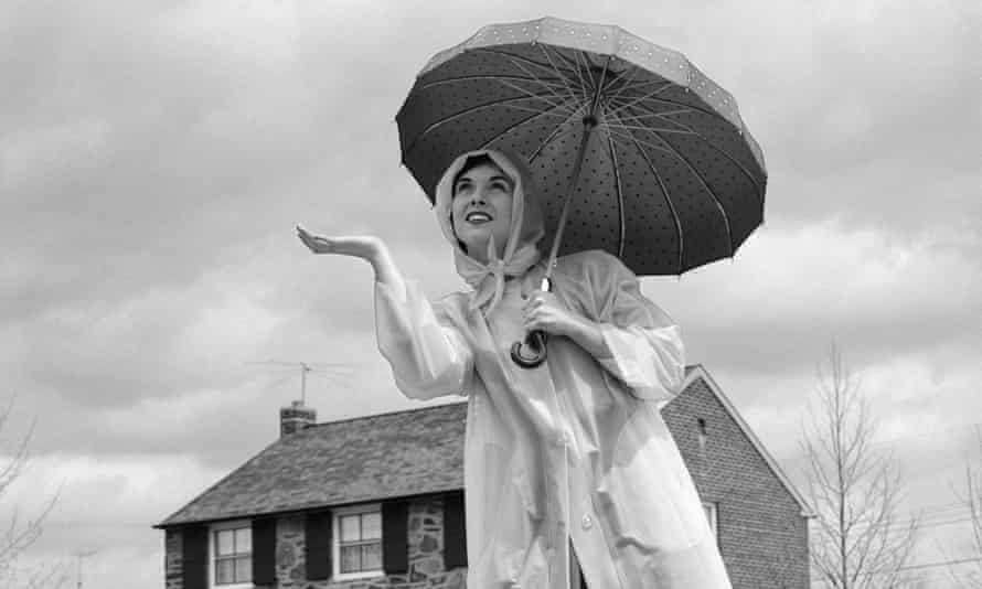 Woman holding an umbrella and wearing a raincoat and rubber boots circa 1950.