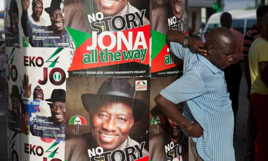 A man stands in front of electoral campaign posters in Lagos, Nigeria, in 2015