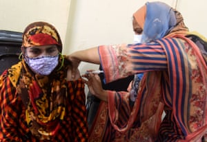A woman receives a shot of the Moderna jab during a mass vaccination campaign at a vaccination center in Dhaka, Bangladesh.
