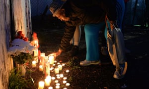 A woman places a candle in front of a makeshift memorial to Akiel Denkins.