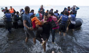 A Syrian refugee carries two children moments after arriving on a dinghy on the Greek island of Lesbos,on Tuesday.