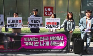 Protesters hold a demonstration denouncing the ad outside a Uniqlo shop in Seoul