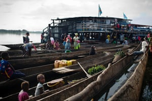 A young girl sits in a pirogue (narrow boat) at the main ferry port in the town of Isangi, in Tshopo province