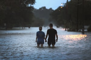 A couple strolls on a road near the shore of Lake Pontchartrain, Louisiana, after it was flooded in the wake of Tropical Storm Barry.