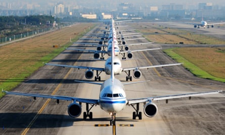 Many airplanes are in line on the runway waiting for take off