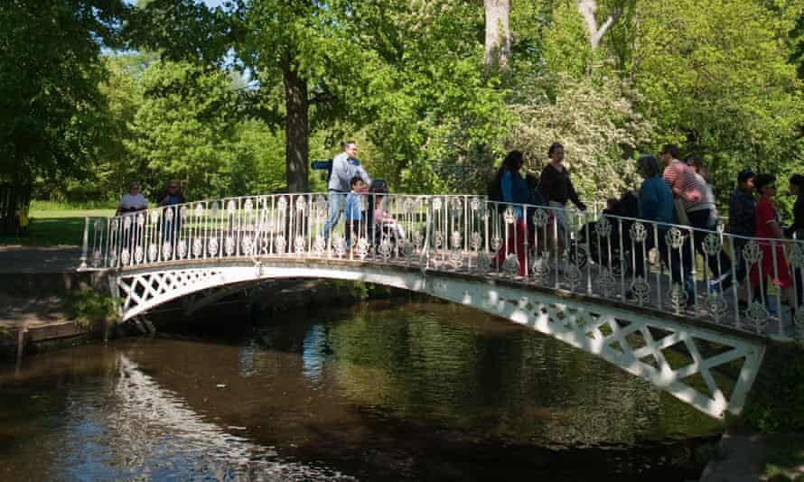 A wrought iron bridge crosses the river Wandle in Morden Hall park.