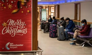 Members of the public in Manchester airport wait next to a poster wishing passengers a merry Christmas