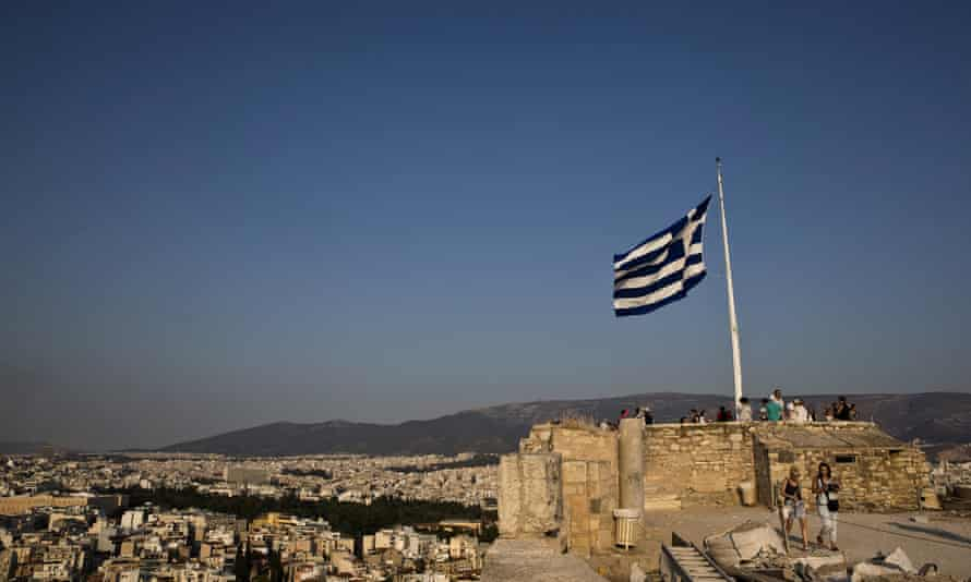 Greek flag flutters in the wind as tourists visit the archaeological site of the Acropolis hill in Athens, GreeceA Greek flag flutters in the wind as tourists visit the archaeological site of the Acropolis hill in Athens, Greece July 26, 2015. REUTERS/Ronen Zvulun/File Photo