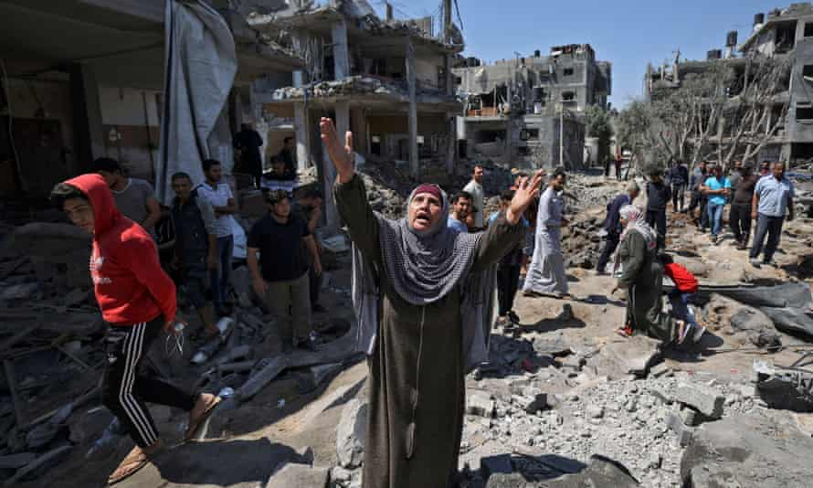 People assess the damage caused by Israeli airstrikes in Beit Hanun, in the northern Gaza Strip