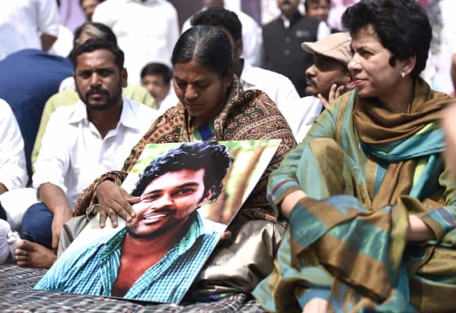 The mother of Dalit PhD student Rohith Vemula cradles a photograph of her son.