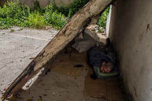 Joniel, 17, sleeps on the ground under a metal slab in an abandoned building site in Las Mercedes