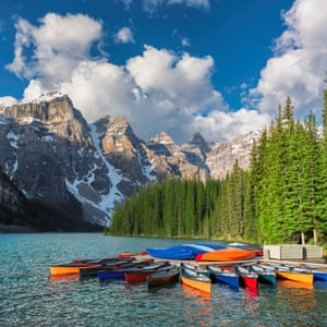 Beautiful sunrise under turquoise waters of the Moraine lake with snow-covered peaks above it in Banff National Park, Canadian Rockies, Canada.