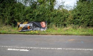 Floral tributes on the B4031 outside RAF Croughton and a sign saying Justice for Harry