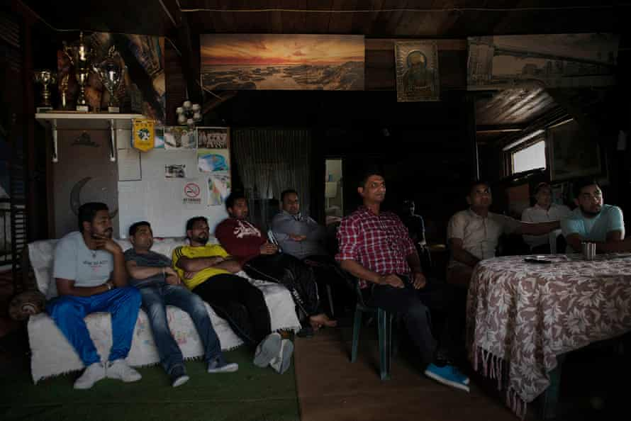 A group of Sikhs unwind by watching an Indian cricket match on TV.