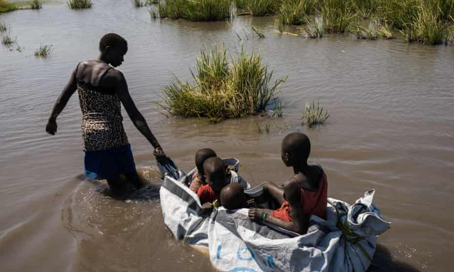 A woman pulls her children with a homemade raft built out of plastic sheeting after receiving a food distribution in Unity State, South Sudan.