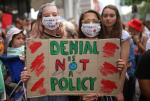 Student activists from School Strike for Climate Australia hold a sign saying 'Denial if not a policy'