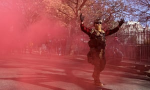 A gun rights advocate wearing body armor and carrying firearms sets off a smoke bomb at the conclusion of a rally near the state capitol building in Richmond, Virginia, on 20 January.