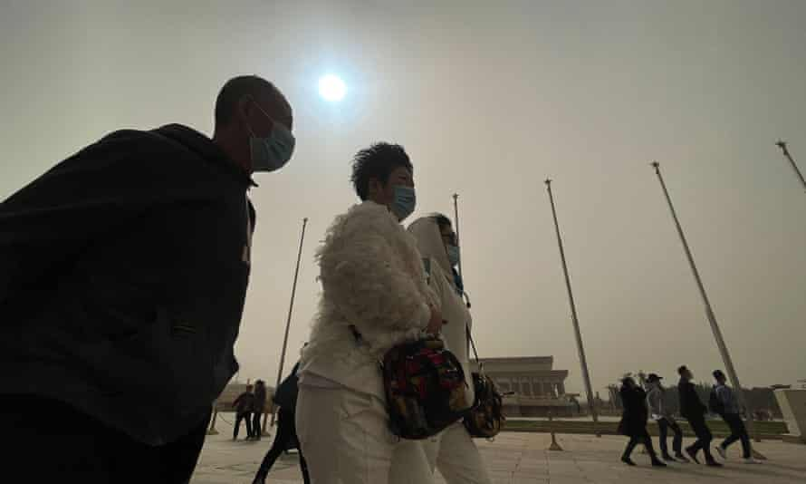 People wear masks to visit Tiananmen square in Beijing. The sun is blue due to dust storms.