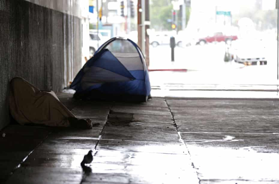 A homeless man huddles under a blanket in Los Angeles.