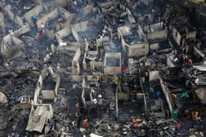 Residents sift through the ruins of their houses after a fire destroyed a squatters' district