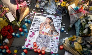 An Ariana Grande poster lies amid tributes left in St Ann's Square to the victims of the terrorist attack in Manchester.