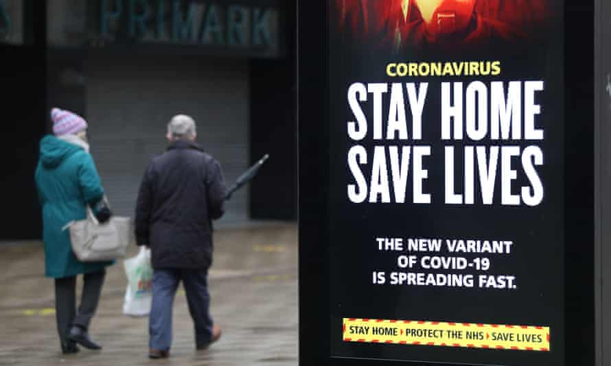 People walk past a 'Stay Home Save Lives' government sign in Portsmouth during England's third national lockdown.
