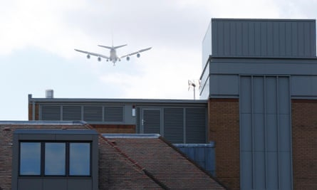 As it approaches Heathrow airport, a 747 passes over office building in Richmond, west London, where the body of a man was discovered.