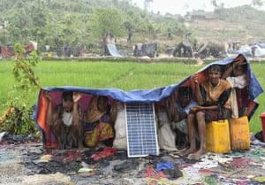 Rohingya refugees protect themself from the rain in Bangladesh's Balukhali refugee camp