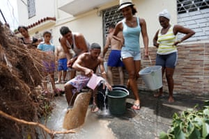 People collect water from a broken tube after Hurricane Irma caused flooding and a blackout in Havana, Cuba.
