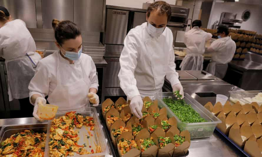 Daniel Humm, right, works to fill to-go boxes of food to donate in the kitchen of Eleven Madison Park in May 2020.