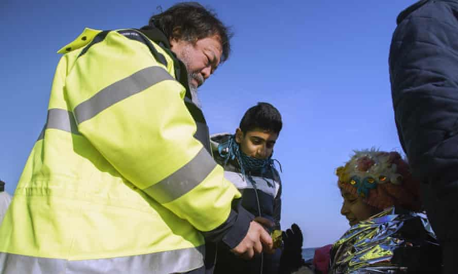 Ai Weiwei gives a chocolate cookie at a girl after her arrival with other asylum seekers on Lesbos.