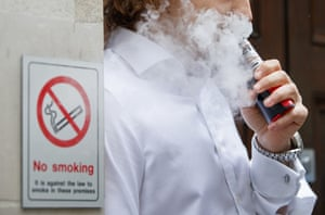 A man is engulfed by vapours as he smokes an e-cigarette.