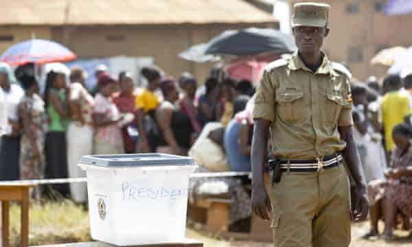 A police officer guards by an empty ballot box at a polling station in Kampala, where five hours after voting was due to start no voting papers had yet arrived.