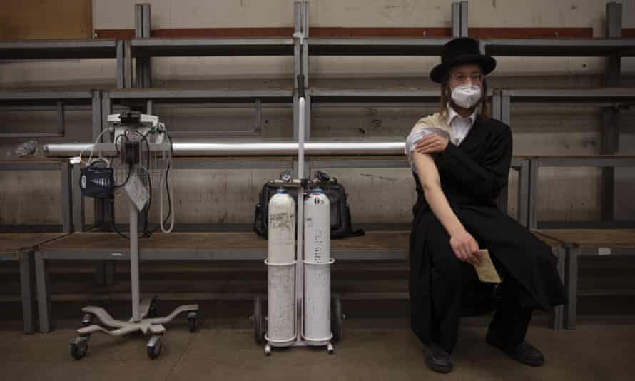 An ultra-Orthodox Jewish man rests after receiving his second dose of the Pfizer vaccine at a synagogue in Bnei Brak, Israel