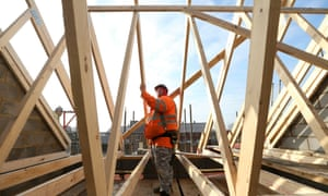 A builder assembles wooden roofing joists on a new home at a Barratt Developments