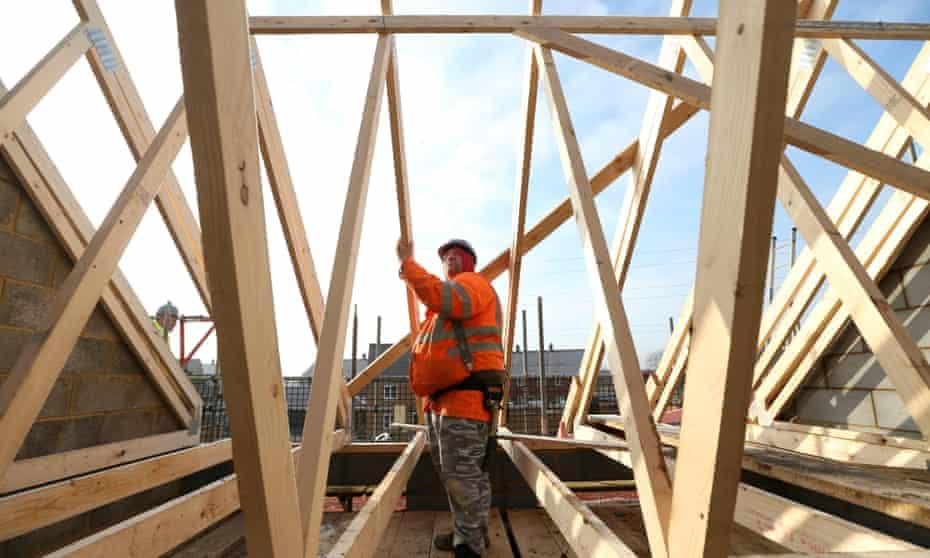 A builder assembles wooden roof joists