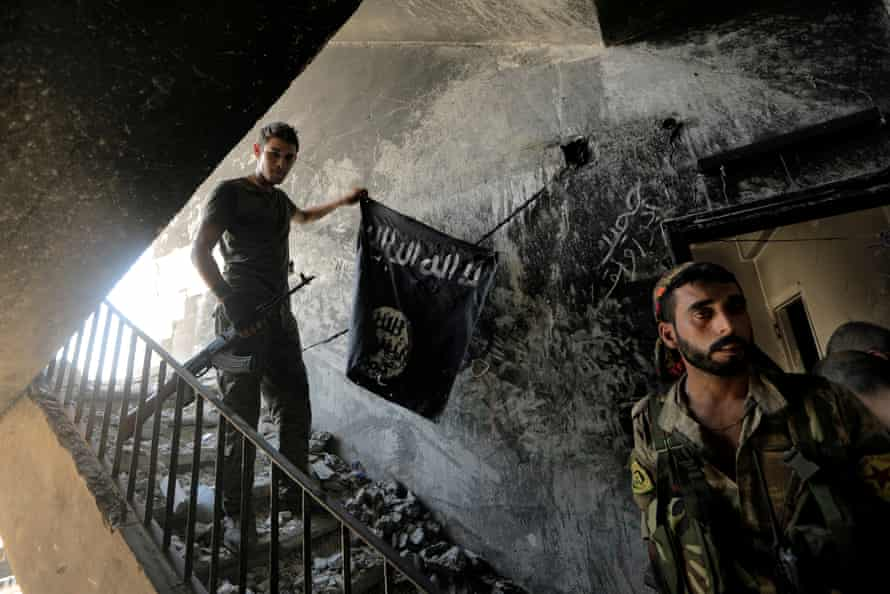 A member of the Syrian Democratic Forces with a black Isis flag found during the fighting with Isis fighters in Raqqa, Syria, 14 August 2017.