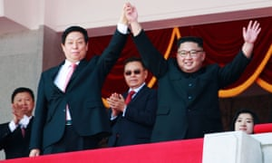 Kim Jong-un and Li Zhanshu, China's third highest ranking official, wave to the crowd during a parade celebrating the 70th anniversary of North Korea's foundation.