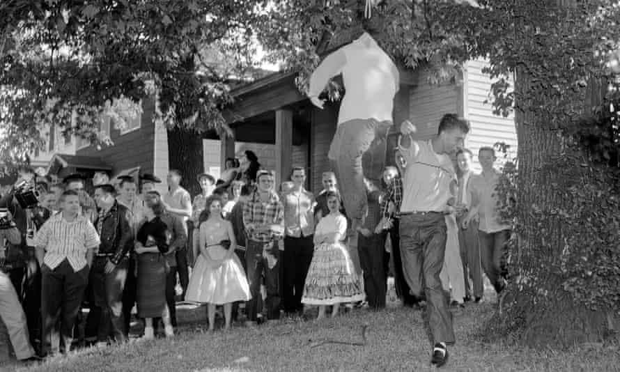An unidentified white student slugs an effigy of a black student outside Central High School in Little Rock, 3 October 1957, as nearly 75 students of the school walked out to protest integration.