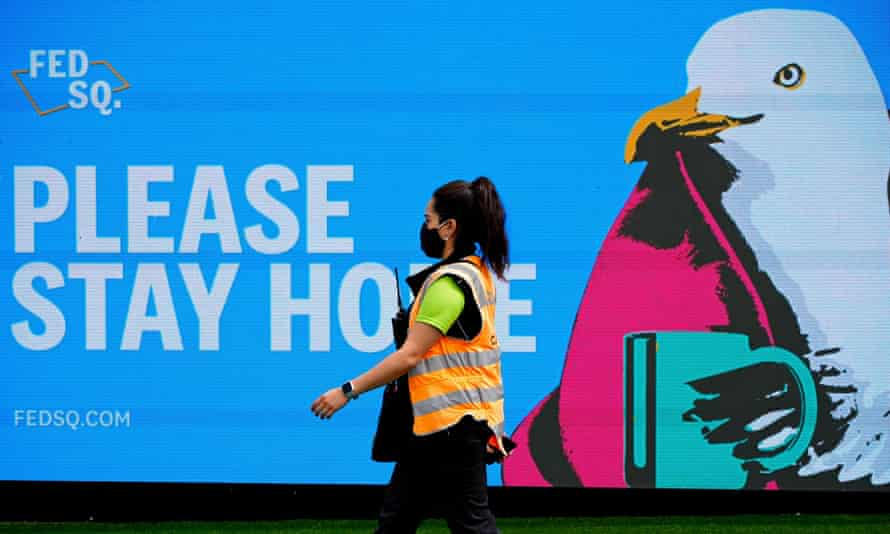 An essential worker walks past a 'Please Stay Home' sign on the first day of a five-day Covid lockdown in Melbourne