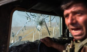 A Kurdish peshmerga fighter leans out of his military vehicle which has taken several direct hits from Isis snipers near Mosul