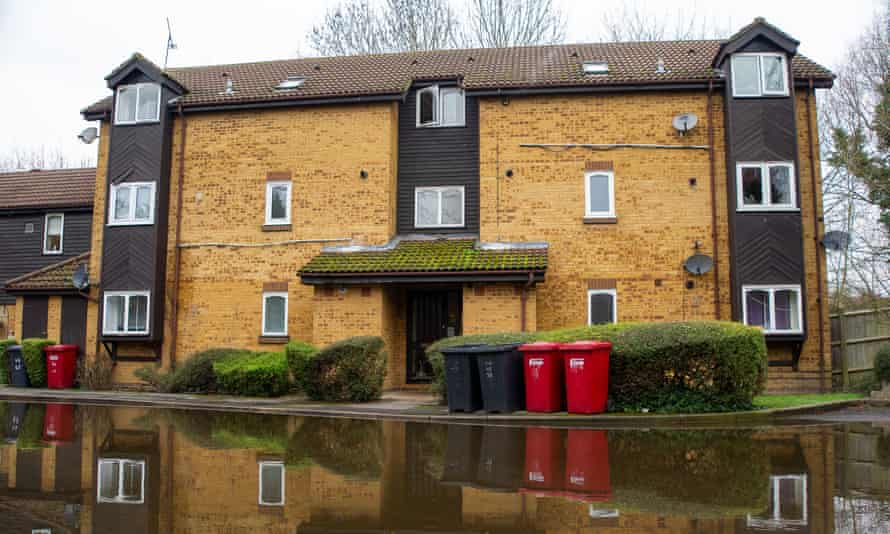block of flats in Colnbrook, Berkshire with road in front completely flooded