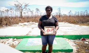 Euridice Kemp stands outside the destroyed home of her grandparents with their portrait in eastern Grand Bahama.