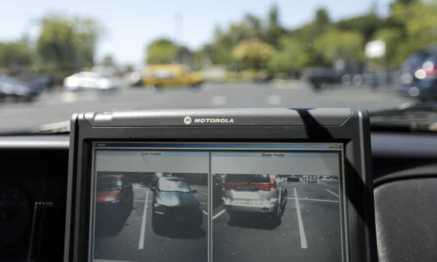 A police vehicle reads the license plates of cars in a parking lot in San Marcos, California.